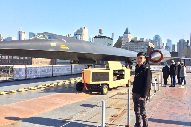Yuxiang Wang stands in front of a military jet.