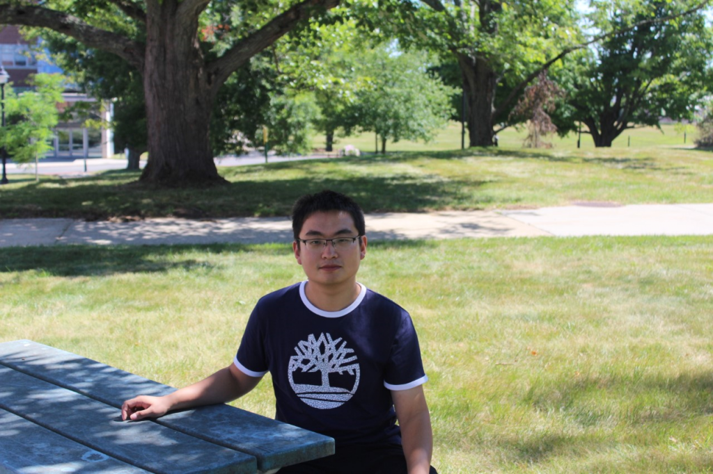 Zhenshan Chen wears a dark tee shirt and sits at a table outside on a summer day.