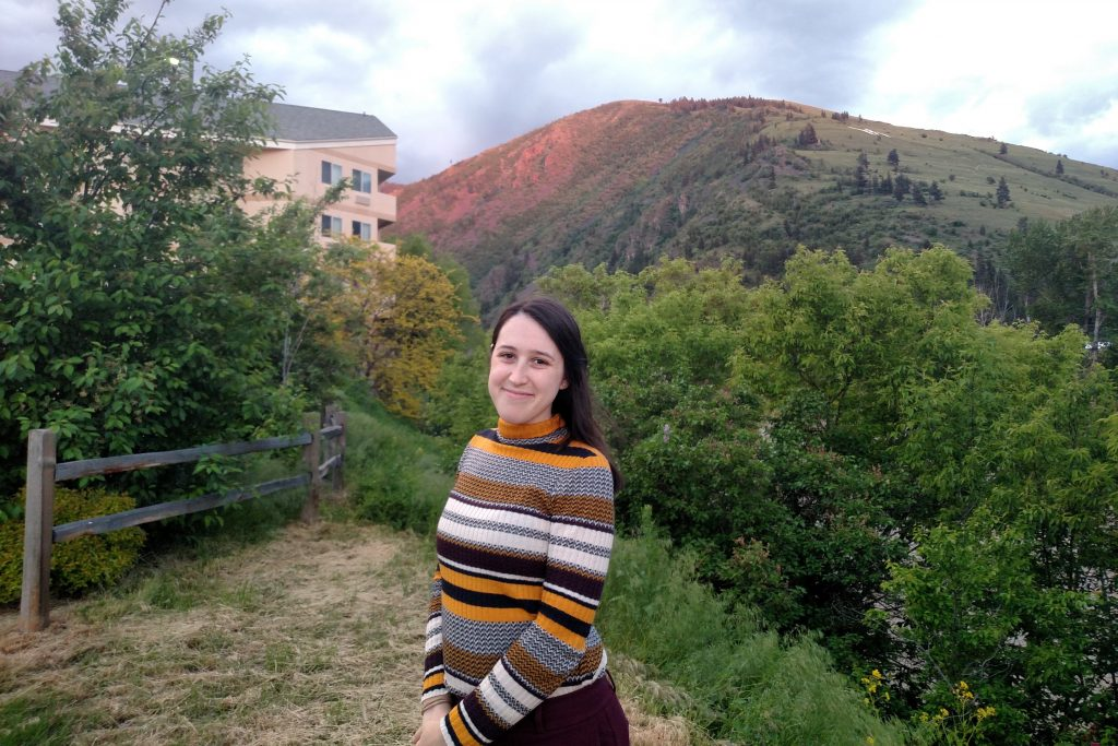 Danielle Tanzer wearing a horizonally striped sweater, standing outdoors with a building and a mountain in the background.