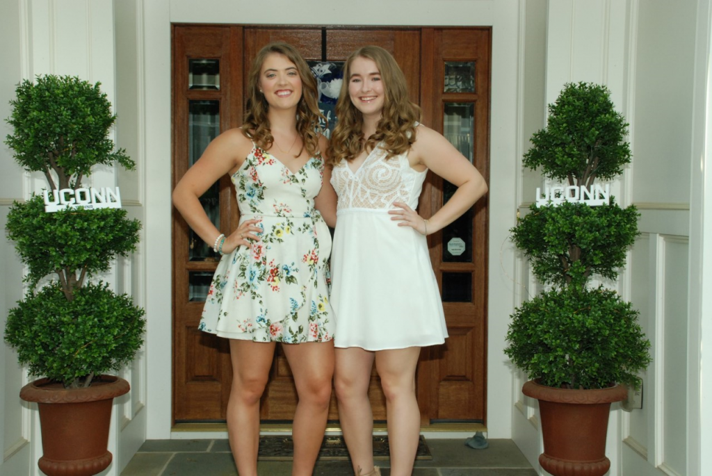 Kristen (left) and Caitlyn Splaine in summer dresses stand in outside an entry door.