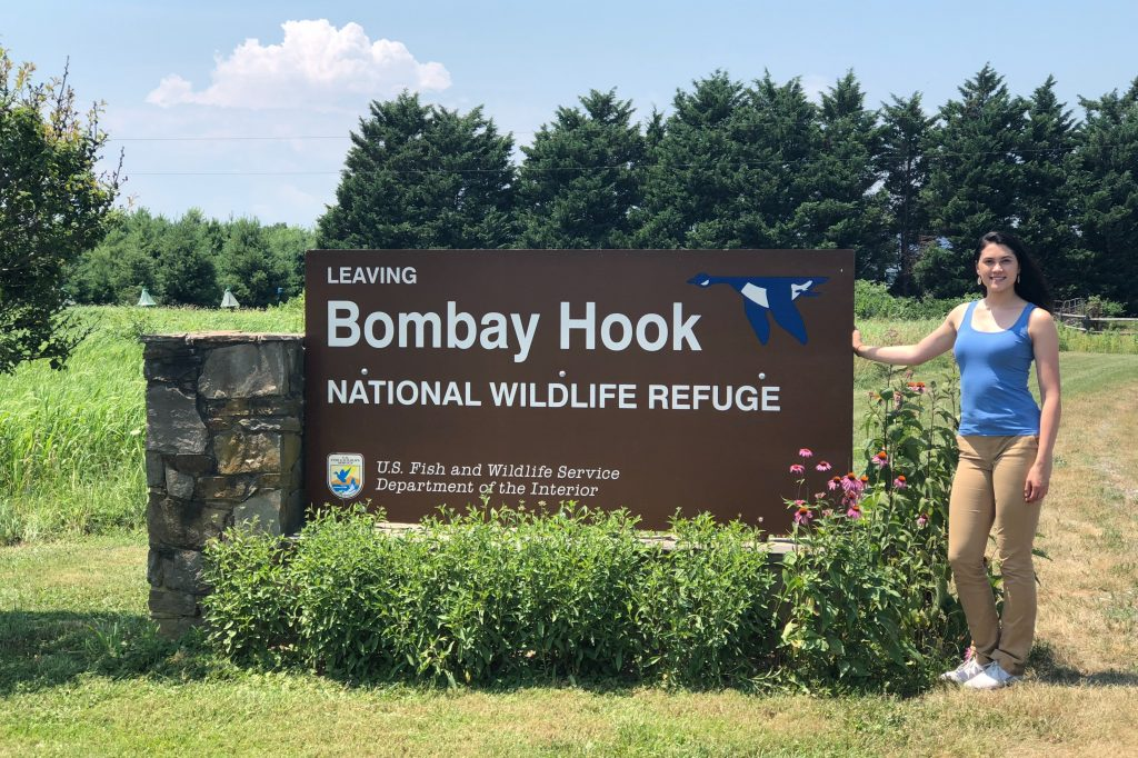 Ava Smith stands next to an outdoor sign for the Bombay Hook Natinal Wildlife Refuge.