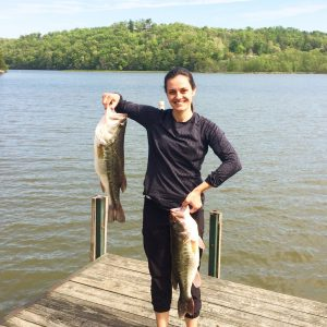 Jessica Brandt holds two bass at Lake Adger in North Carolina, where she conducted dissertation research on the coal ash waste stream.