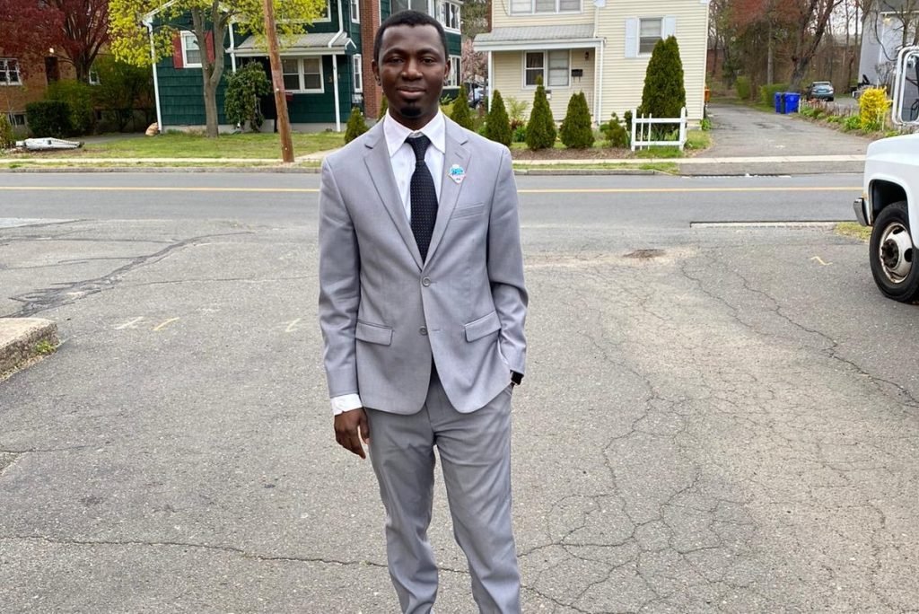 Eric Atanga wears a light gray suit and stands outdoors in a driveway.