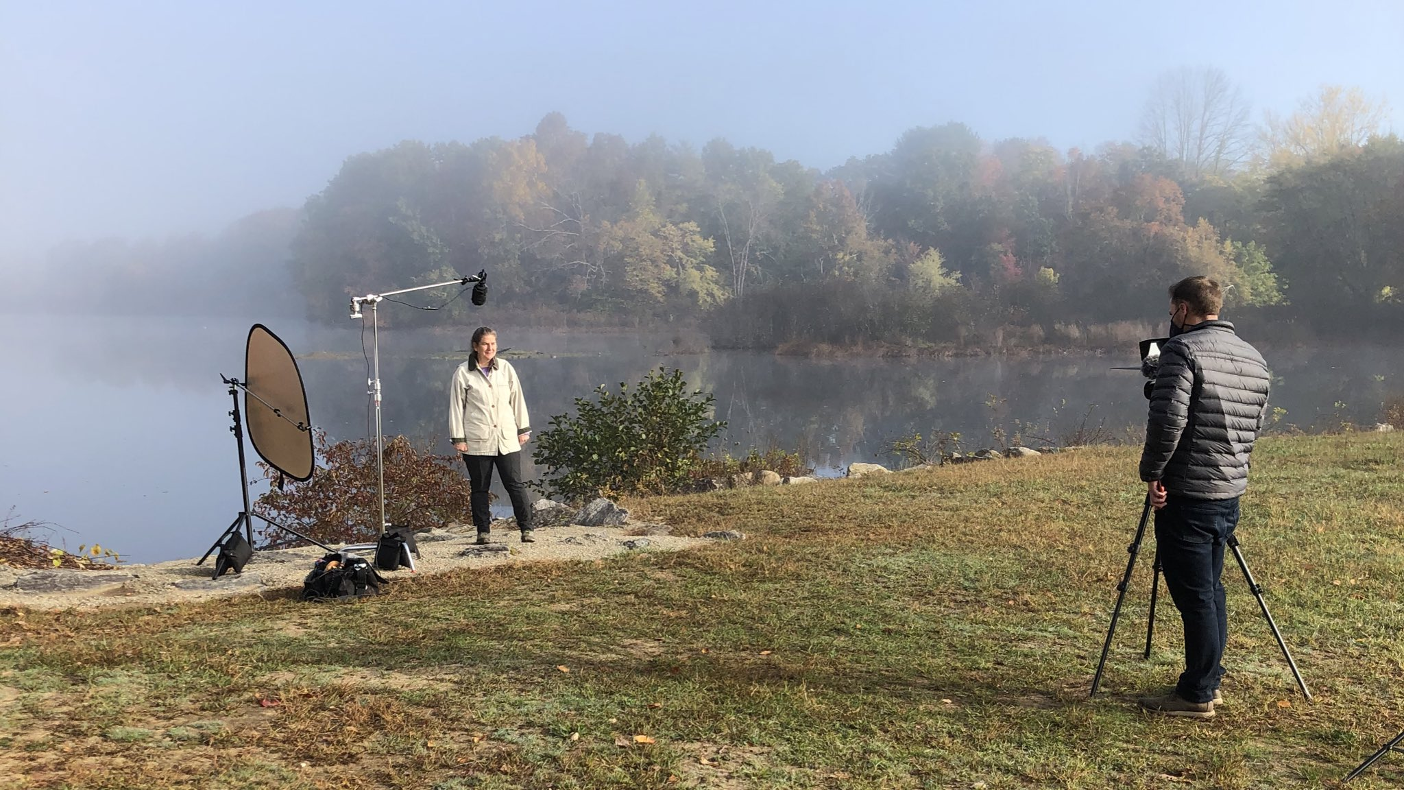 Filming crew at the edge of a lake in autumn