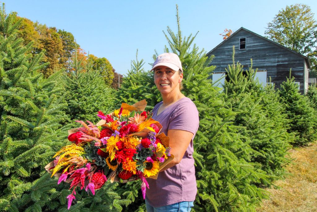 Jen Syme holding a large bouquet of flowers and standing in front of Christmas trees growing in a field.