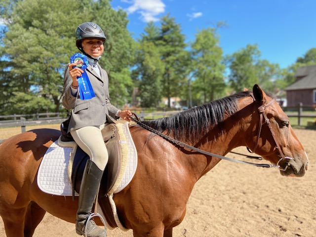 girl riding a horse and showing off a blue ribbon