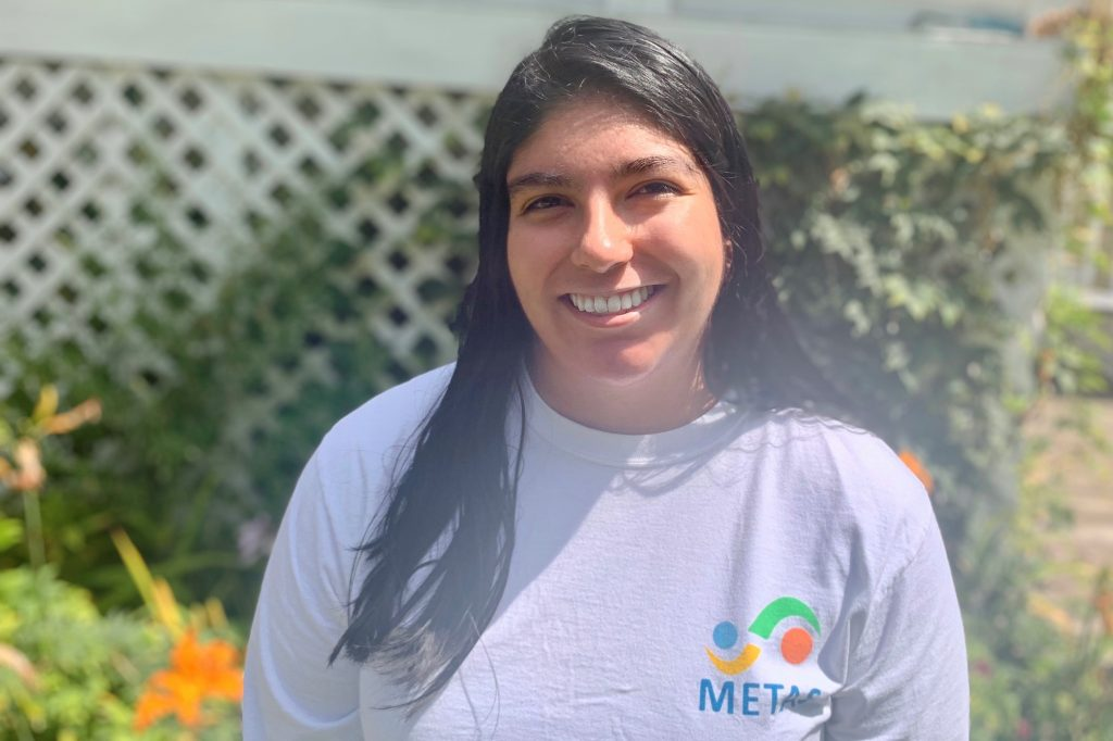 Jacqueline Cuevas Gonzales, wearing a white t-shirt, stands outside on a sunny day, with a white fence and flower bed in the background.