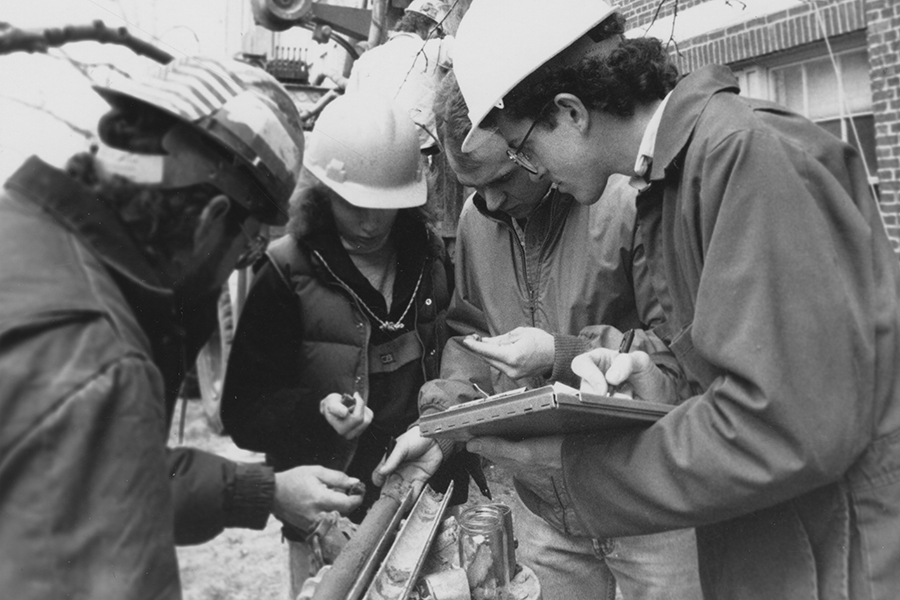 A group of people looking at a core sample